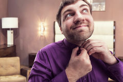 Bearded man buttons his shirt Royalty Free Stock Photo