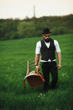 Bearded man carries a chair on the field Stock Photos