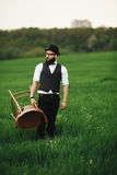 Bearded man carries a chair on the field Royalty Free Stock Photos