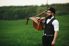 Bearded man carries a chair on the field Stock Images