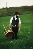 Bearded man carries a chair on the field Stock Photography
