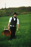Bearded man carries a chair on the field Royalty Free Stock Photo