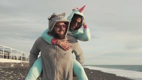 Bearded man is carrying on back her cheerful girlfriend, walking over sea coast. Woman is astride on her boyfriend, smiling and laughing. They are wearing stock footage
