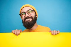 Bearded man carrying heavy sign. Bearded man in glasses carrying heavy yellow board on blue background Stock Images