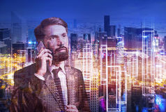 Bearded man on cell phone and the city. Portrait of bearded businessman on his phone standing against large night cityscape. Double exposure. Toned image Royalty Free Stock Photo