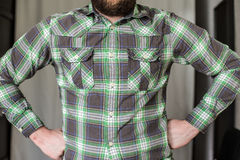 Bearded man in a checked shirt standing arms akimbo. Stout, bearded man in a checked shirt standing arms akimbo resolutely Stock Photos