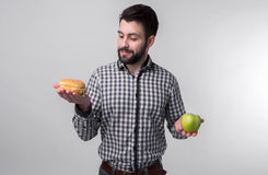 Bearded man in checkered shirt on a light background holding a hamburger and an apple. Guy makes the choice between fast Stock Photo