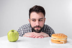 Bearded man in checkered shirt on a light background holding a hamburger and an apple. Guy makes the choice between fast royalty free stock image