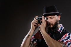 Bearded man in a checkered shirt taking a photo Stock Photo