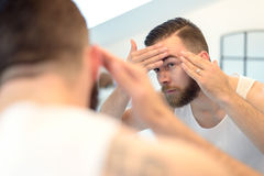 Bearded man checking his complexion. In the bathroom mirror, looking concerned, rear view over the shoulder royalty free stock images