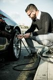 Bearded man checking tire pressure Royalty Free Stock Images