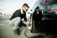 Bearded man checking tire pressure Stock Images