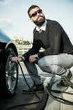 Bearded man checking tire pressure Stock Photography