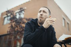 Bearded man chewing sandwich at the street. stock photography