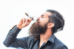 Bearded man with cigar. Handsome bearded tough rich man with stylish hair mustache and long beard on serious face in blue fashion shirt smoking cigar isolated on royalty free stock image