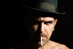 Bearded man with cigarette. Portrait closeup young handsome sensual unshaven frown bearded man model with cigarette wearing felt hat studio play of light and Stock Image