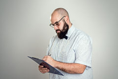 Bearded man with clipboard in front of gray background Royalty Free Stock Image