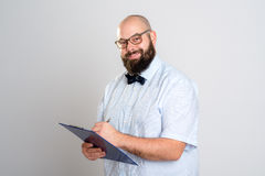 Bearded man with clipboard in front of gray background Stock Photo