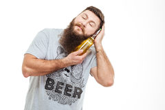 Bearded man with closed eyes enjoying bottle of beer Royalty Free Stock Photos