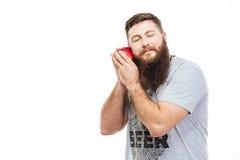Bearded man with closed eyes holding apple near the cheek Royalty Free Stock Photo