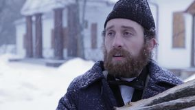 Bearded man in clothes of 19 centuries with wood in his hands, Russian winter stock footage
