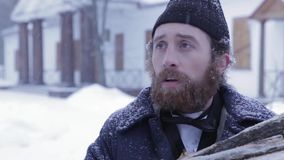 Bearded man in clothes of 19 centuries with wood in his hands, Russian winter stock video