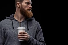 Bearded man with coffee in hand. Dramatic shot of handsome young bearded man in gray hoodie having coffee Male taking rest and drinking fresh morning coffee to stock image