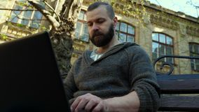 The bearded man communicates with friends in a social network typing text on a laptop. In the park stock video footage