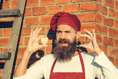 Bearded man cook chef. Handsome bearded man cook chef uniform and red hat with long beard standing with dough in shape of heart on stony wall with ladder on stock images