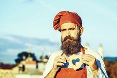 Bearded man cook chef. Handsome bearded man cook chef uniform and red hat with long beard standing with dough in shape of heart on sunny day outdoor on blue sky royalty free stock image