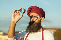 Bearded man cook chef. Handsome bearded man cook chef uniform and red hat with long beard standing with mold in shape of heart on sunny day outdoor on blue sky royalty free stock photography