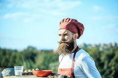 Bearded man cook chef. Handsome bearded man cook chef uniform and red hat with long beard standing near table with bowl and glass of milk in sunny day outdoor on royalty free stock image