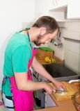 A bearded man cooks in the kitchen, cuts onions royalty free stock photo