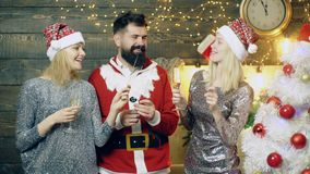 The bearded man in costume santas and two girls in the New Year`s hats drink champagne and burn sparkles lights against. The background of New Year`s scenery stock video footage