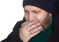 Bearded man coughs, covering his mouth with a handkerchief. A simple bearded man with a sore throat in a blue down jacket and a blue knitted hat coughs covering Royalty Free Stock Image