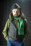 A bearded man covered a hat. Portrait of a bearded man covered a hat with a green scarf hands in his pockets Stock Image