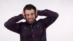 Bearded man covering his ears from a loud noise. Handsome man protecting his ears from extremely loud noises or screaming. Overthinking, anxiety, stress royalty free stock images