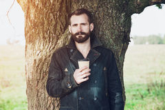 Bearded man with cup of coffee in park Stock Photography