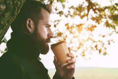 Bearded man with cup of morning coffee walking Stock Photo