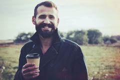 Bearded man with cup of morning coffee walking in park Royalty Free Stock Image