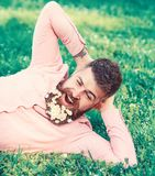 Bearded man with daisy flowers in beard lay on meadow, lean on hand, grass background. Man with beard on yawning face. Have rest. Hipster with bouquet of stock photo