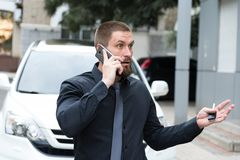 A bearded man in dark clothes, emotionally talking on the phone. Near the car Stock Photography