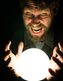 Bearded man in the dark, holding in front of a lamp, expresses different emotions Stock Photography