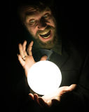 Bearded man in the dark, holding in front of a lamp, expresses different emotions Royalty Free Stock Images