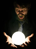 Bearded man in the dark, holding in front of a lamp, expresses different emotions Stock Image