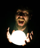 Bearded man in the dark, holding in front of a lamp, expresses different emotions Royalty Free Stock Photos