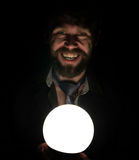 Bearded man in the dark, holding in front of a lamp, expresses different emotions. Royalty Free Stock Photography