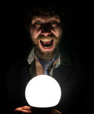 Bearded man in the dark, holding in front of a lamp, expresses different emotions. Stock Photo
