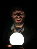 Bearded man in the dark, holding in front of a lamp, expresses different emotions. Stock Image