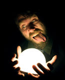 Bearded man in the dark, holding in front of a lamp, expresses different emotions Royalty Free Stock Photography